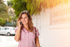 Smiling young woman speaking on cell phone Royalty Free Stock Photos