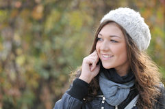 Smiling young woman speaking at phone Royalty Free Stock Image