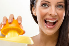 Smiling young woman squeezes fresh orange juice Royalty Free Stock Photos