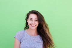 Smiling young woman standing against green background. Front portrait of smiling young woman standing against green background Stock Images