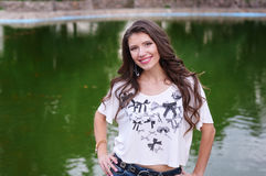 Smiling young woman standing on the background of the lake in the park Stock Photography