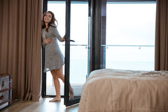 Smiling young woman standing barefoot near the big glass door Stock Image