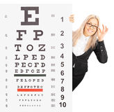 Smiling young woman standing behind an eyesight test Royalty Free Stock Photography