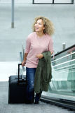 Smiling young woman standing on escalator with suitcase Royalty Free Stock Photography