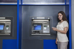 Smiling young woman standing in front of an ATM and looking at her phone Royalty Free Stock Photography