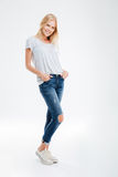 Smiling young woman standing with hands in pockets Stock Images