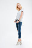 Smiling young woman standing with hands in pockets on tiptoe Royalty Free Stock Photo