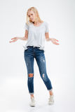 Smiling young woman standing with hands in pockets on tiptoe Stock Images