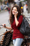 Smiling young woman standing outdoors and using mobile phone Royalty Free Stock Image