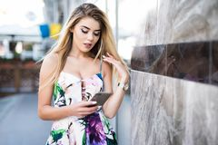 Smiling young woman standing with phone near building on summer city street. Smiling young woman standing with phone near building on summer street Royalty Free Stock Photo