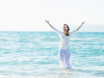 Smiling young woman standing in sea and sprinkling water Stock Image