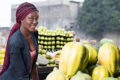 Smiling young woman standing between fruit shelves. Smiling young woman standing between shelves of fruit and looking at the camera Royalty Free Stock Images