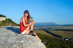Smiling young woman standing on the top of mountain Stock Image