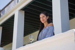 Smiling young woman standing by wineglass in balcony. Low angle view of smiling young woman standing by wineglass in balcony Stock Image