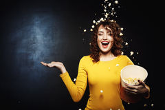 Smiling young woman staying under popcorn shower with right hand up. Isolated on black background Stock Photos