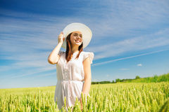 Smiling young woman in straw hat on cereal field Stock Photo
