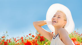 Smiling young woman in straw hat on poppy field Stock Images