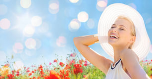 Smiling young woman in straw hat on poppy field Stock Photos
