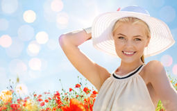 Smiling young woman in straw hat on poppy field. Happiness, nature, summer, vacation and people concept - smiling young woman with closed eyes wearing straw hat Royalty Free Stock Photos