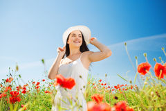 Smiling young woman in straw hat on poppy field. Happiness, nature, summer, vacation and people concept - smiling young woman wearing straw hat on poppy field Royalty Free Stock Photography