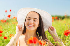 Smiling young woman in straw hat on poppy field Royalty Free Stock Photography