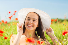 Smiling young woman in straw hat on poppy field Royalty Free Stock Photo