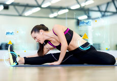 Smiling young woman stretching on mat in gym Stock Images
