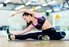 Smiling young woman stretching on mat in gym Royalty Free Stock Image