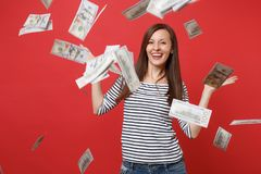 Smiling young woman in striped clothes spreading hands, scattering lots of dollars, standing under money banknotes royalty free stock photography