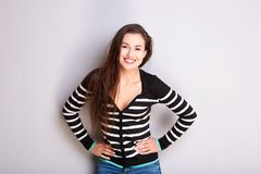 Smiling young woman in striped sweater against gray wall. Portrait of smiling young woman in striped sweater against gray wall Royalty Free Stock Image