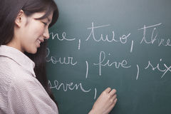 Smiling young woman student writing English numbers on blackboard stock images