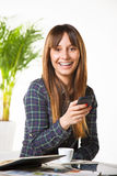Smiling young woman subject a phone in the office Stock Photo
