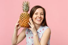 Smiling young woman in summer clothes holding in hands fresh ripe pineapple fruit isolated on pink pastel wall. Background in studio. People vivid lifestyle stock image
