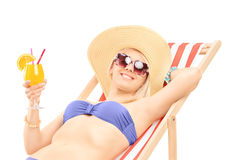Smiling young woman sunbathing and holding a cocktail. Isolated on white background Stock Photography