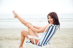 Smiling young woman sunbathing in lounge on beach Royalty Free Stock Photos