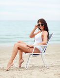 Smiling young woman sunbathing in lounge on beach Royalty Free Stock Photo
