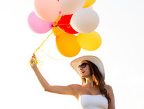 Smiling young woman in sunglasses with balloons Stock Photo