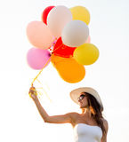Smiling young woman in sunglasses with balloons Stock Image
