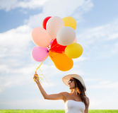 Smiling young woman in sunglasses with balloons Royalty Free Stock Image