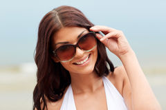 Smiling young woman with sunglasses on beach. Summer vacation, tourism, travel, holidays and people concept -face of smiling young woman with sunglasses on beach Royalty Free Stock Photo