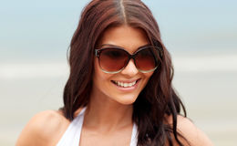 Smiling young woman with sunglasses on beach. Summer vacation, tourism, travel, holidays and people concept -face of smiling young woman with sunglasses on beach Stock Images