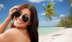 Smiling young woman with sunglasses on beach Royalty Free Stock Image
