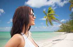 Smiling young woman with sunglasses on beach Stock Photography