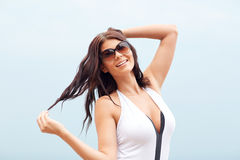 Smiling young woman with sunglasses on beach Stock Photos