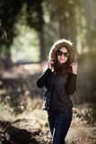 Smiling young woman with sunglasses in forest Stock Image