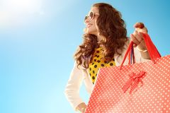 Woman looking into distance with shopping bags against blue sky Stock Images