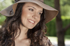 Smiling young woman in sunhat looking away in park Royalty Free Stock Photos