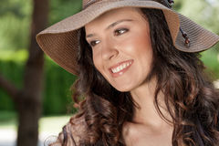 Smiling young woman in sunhat looking away in park stock image