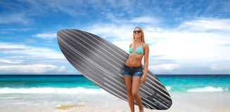 Smiling young woman with surfboard on beach Royalty Free Stock Photo