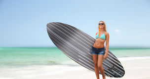 Smiling young woman with surfboard on beach Royalty Free Stock Images